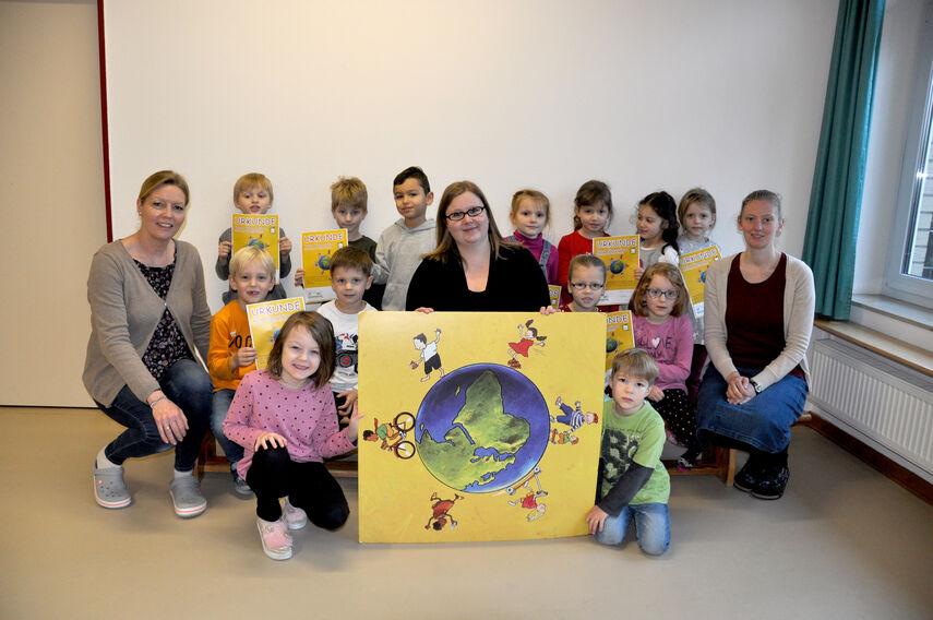 13 Kinder und 3 Frauen knien hinter einem Kindermeilen-Plakat.