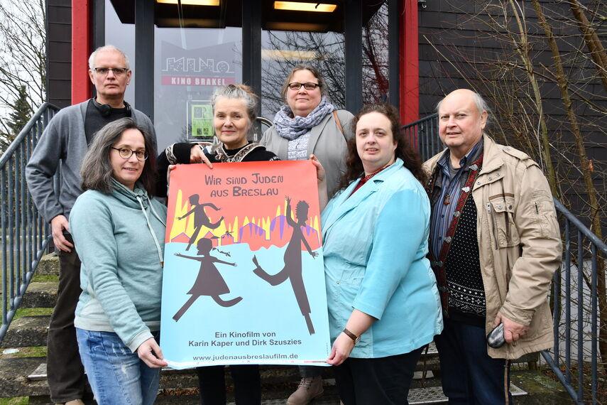 6 Personen stehen vor dem Brakeler Kino und halten gemeinsam ein Plakat in der Hand. Auf dem Plakat steht 'Wir sind Juden aus Breslau'.