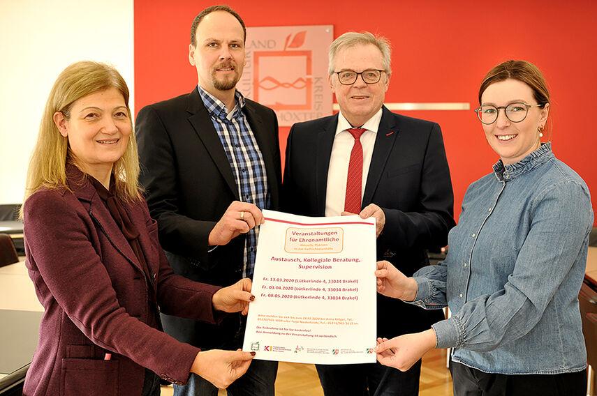 4 Personen halten gemeinsam ein Plakat zum Thema 'Veranstaltungen für Ehrenamtliche' in den Händen.