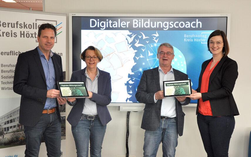 4 Personen halten Tablets in der Hand und werben für den digitalen Bildungscoach.