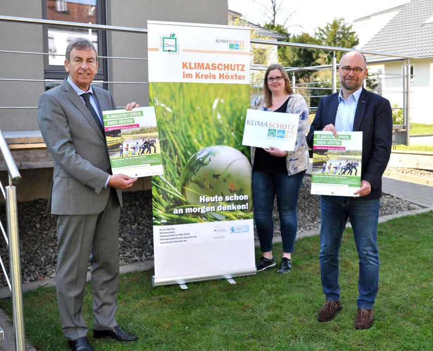 Landrat Friedhelm Spieker, Carolin Röttger und Michael Werner stehen vor einem Rollbanner und werben für den Klimaschutzpreis.