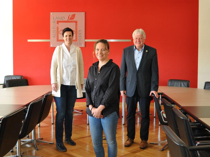 Frau Ribbentrup, Frau Merkel und Herr Brune stehen im Sitzungsraum der Kreisvewaltung.