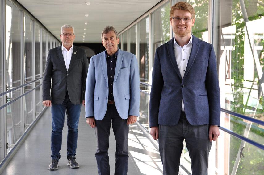 Gerhard Handermann und Friedhelm Spieler stellen Manuel Pawlik als neuen Abteilungsleiter vor. Sie stehen im Glasflur der Kreisverwaltung Höxter.