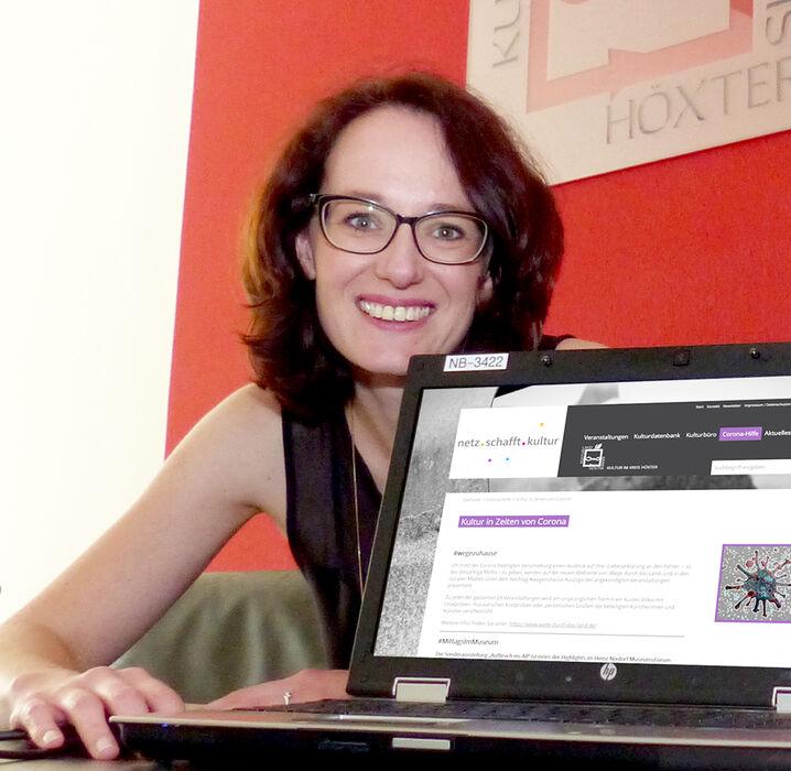 Julia Siebeck sitzt hinter einen Laptop und zeigt die Internetseite von www.netzschafftkultur.de