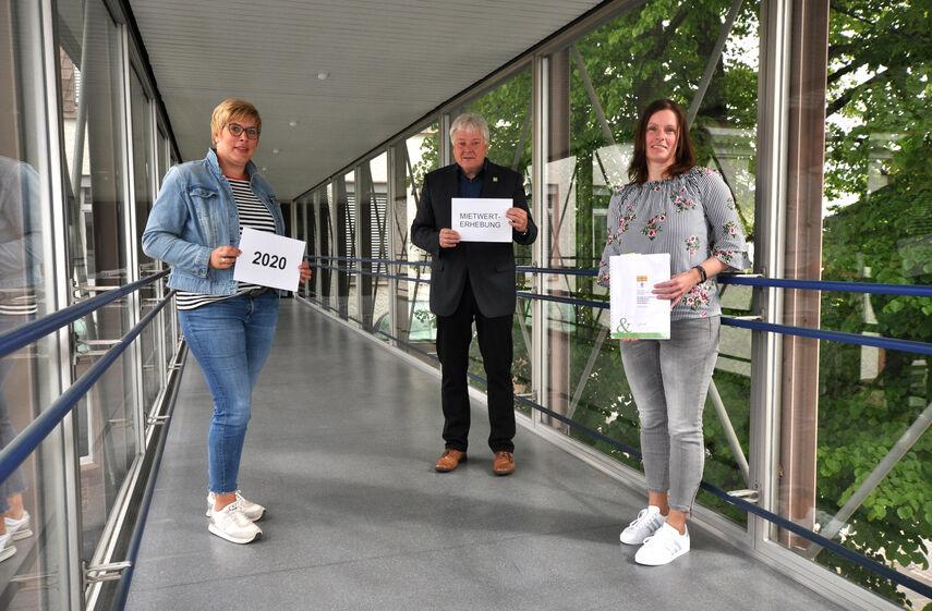 Frau Lüke, Herr Brune und Frau Müller stehen im Glasflur der Kreisverwaltung Höxter.