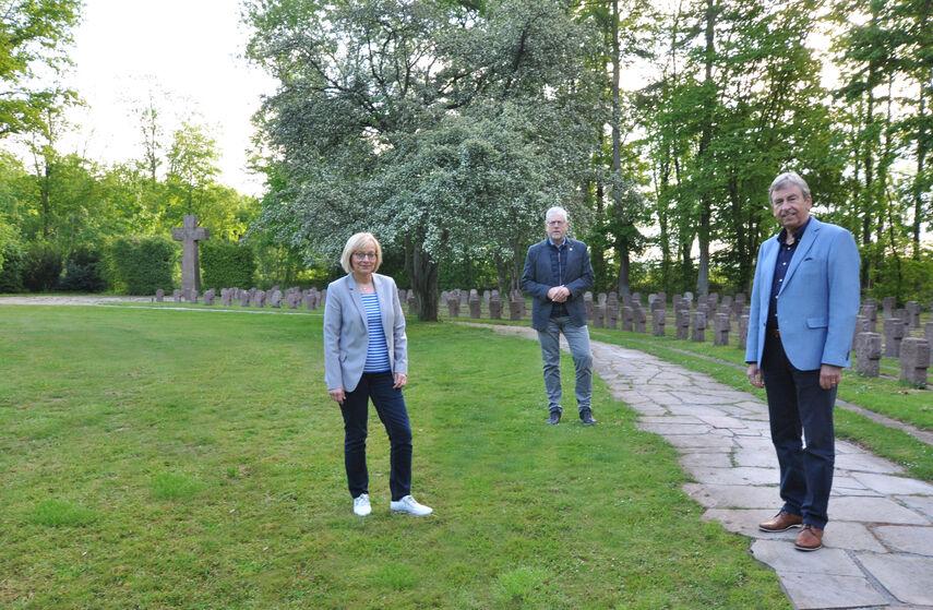 Elisabeth Henneke, Gerhard Handermann und Landrat Friedhelm Spieker stehen auf einem Friedhof.