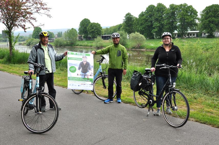Friedhelm Spieker, Michael Stickel und Caronlin Röttger stehen mit ihren Rädern am Weserradweg und werben für die Aktion Stadtradeln.
