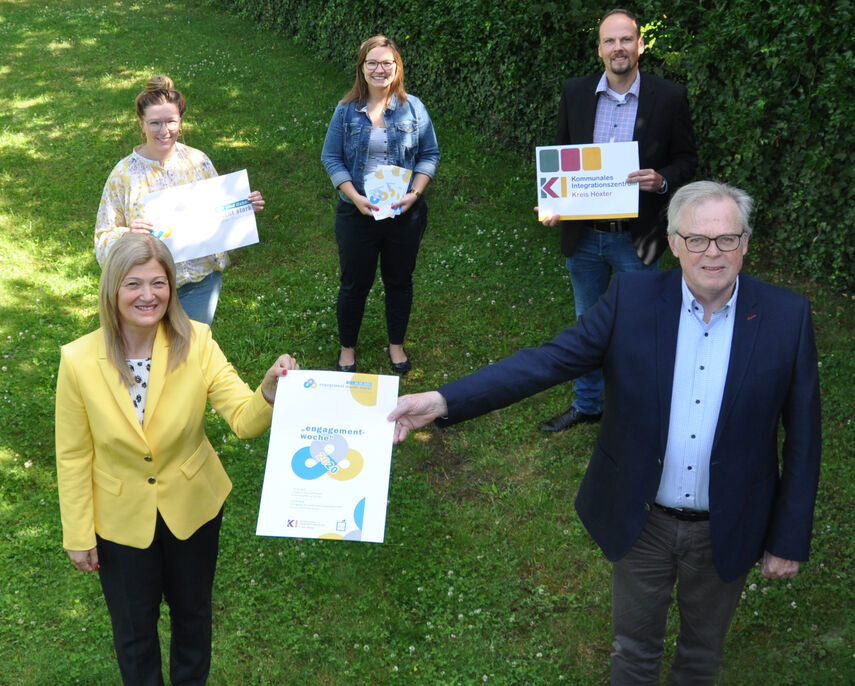 5 Personen stehen im Garten und halten Flyer und Plakate für die Engagementwoche in den Händen.