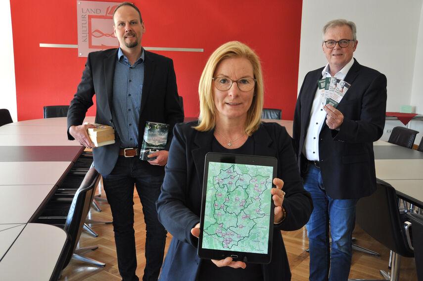 Klaus Schumacher, Petra Sonntag und Dominic Gehle stellen Online-Kartendienst vor und halten eine Tablet, Flyer und Bücher in den Händen.