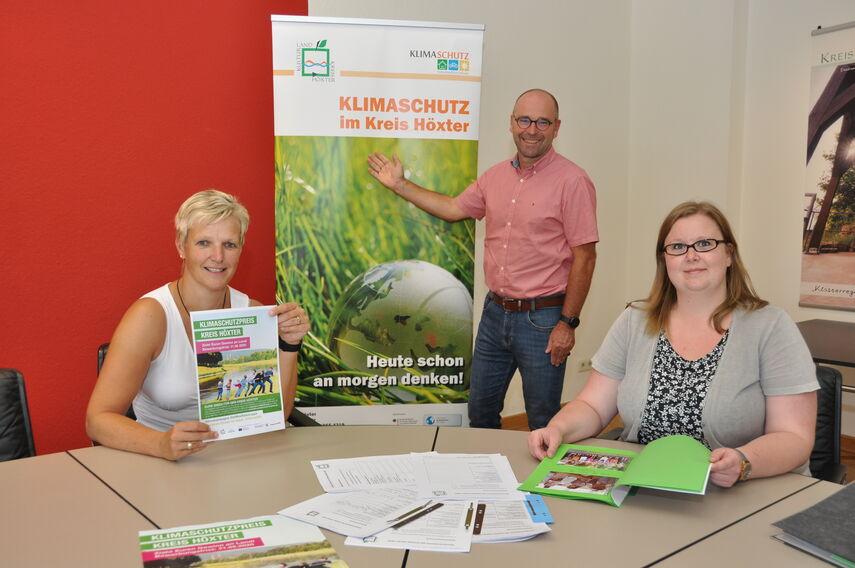 Michael Werner, Dr. Kathrin Weiß und Carolin Röttger werben vor einem Rollbanner für den Klimaschutzpreis.
