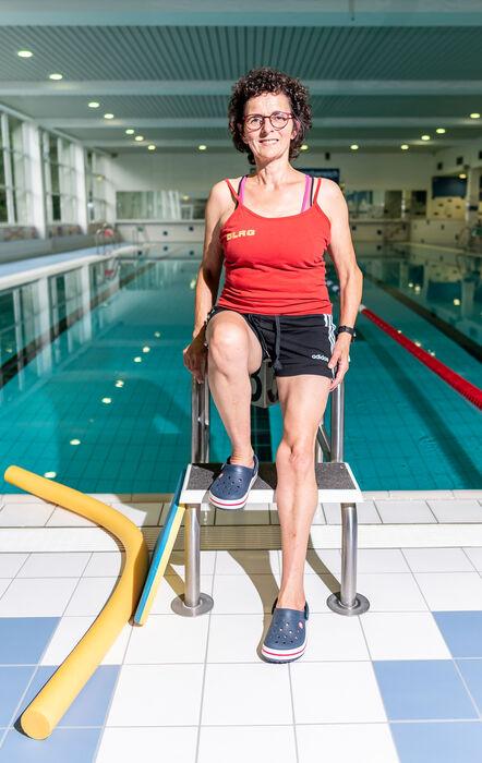 Schwimmtrainerin Friederike Starke sitzt auf einem Startblock im Hallenbad Brakel.