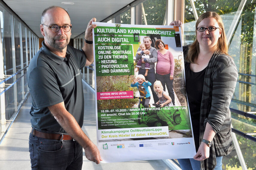 Michael Werner und Carolin Röttger halten ein Plakat in den Händen zum Thema Online-Vorträge zum Klimaschutz.