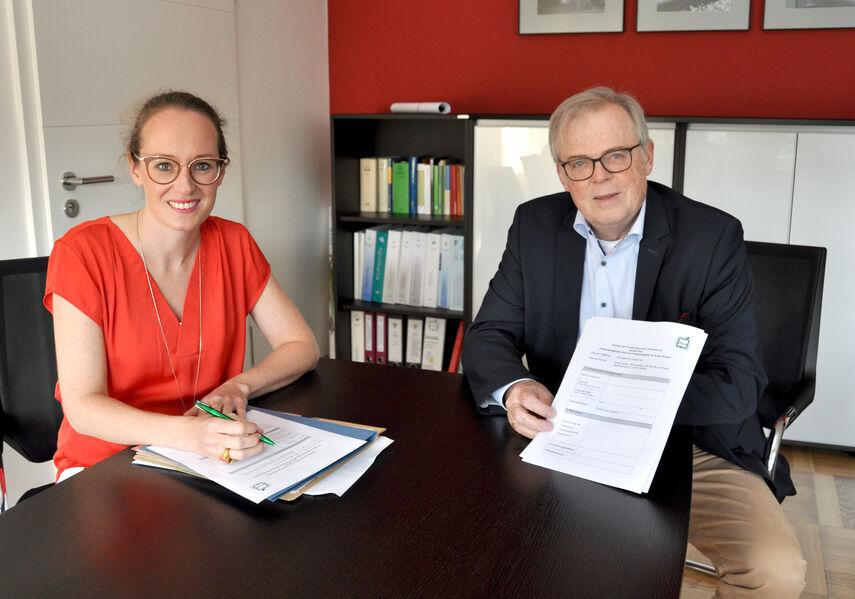 Julia Siebeck und Klaus Schumacher füllen am Schreibtisch Formulare aus.