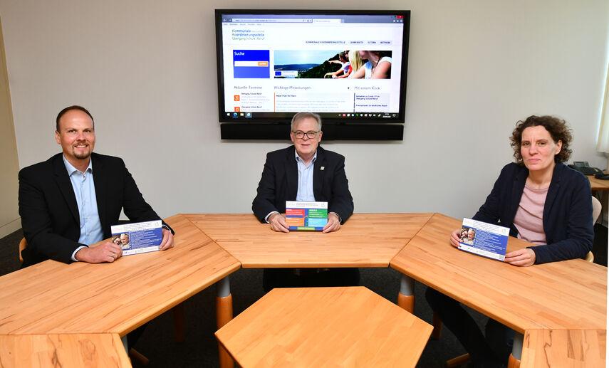 3 Personen sitzen im Sitzungsraum vor einem großen Bildschirm und präsentieren die neue Internetseite 'Koko'.