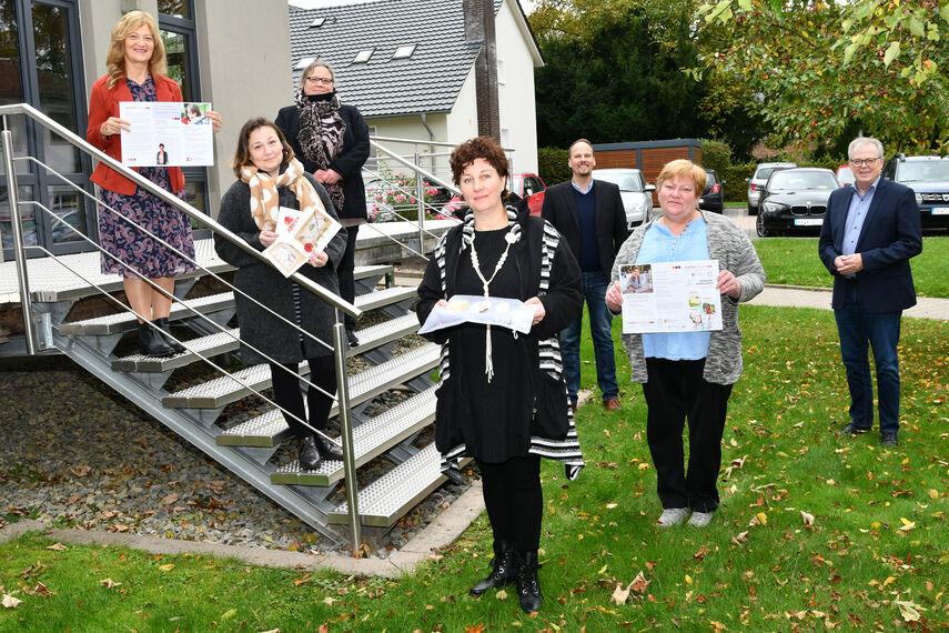 7 Personen stehen auf bzw. vor einer Treppe und werben für einen Mitmachworkshop