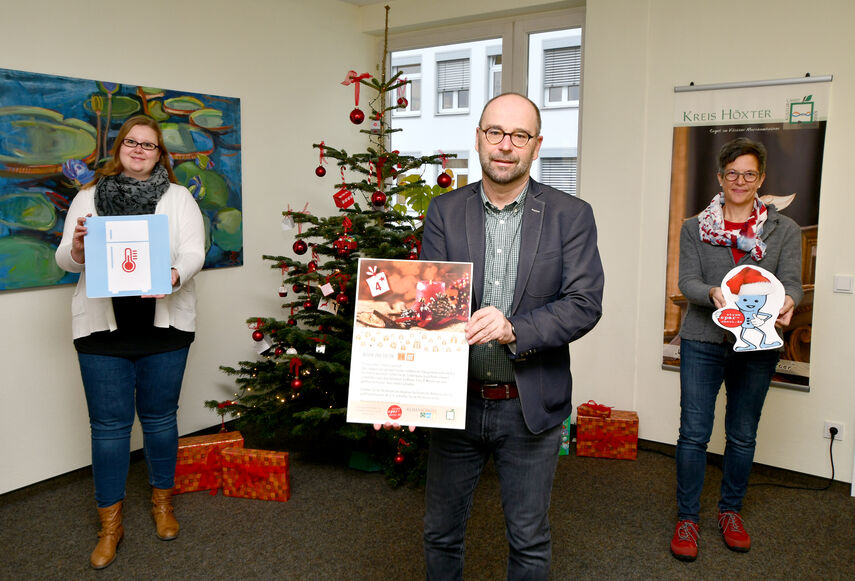 Caroline Röttger, Michaela Werner und Martina Krog stehen vor einem Weihnachtsbaum und halten einen großen Adventskalender in der Hand.