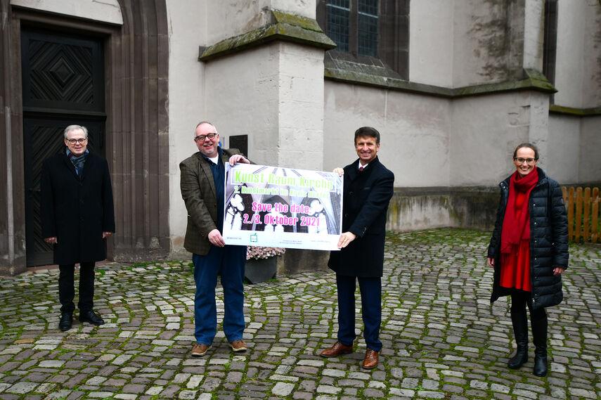 4 Personen vor einer Höxteraner Kirche weisen mit einem Plakat auf den 1. Kunstmarkt im Kreis Höxter hin.