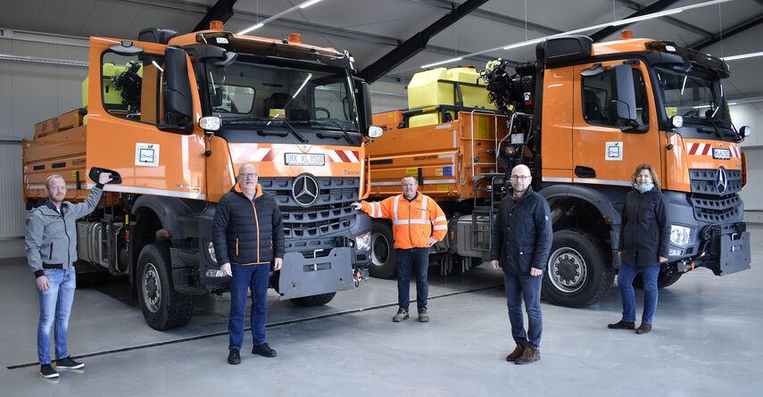 4 Personen stehen vor 2 neuen Fahrzeugen in einer Halle, die für den Winterdienst angeschafft wurden.