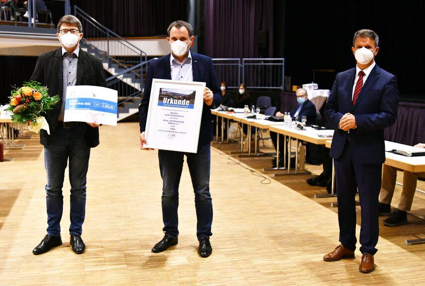 3 Personen halten die Urkunde für den Heimatpreis für das Haus Krus in der Hand.