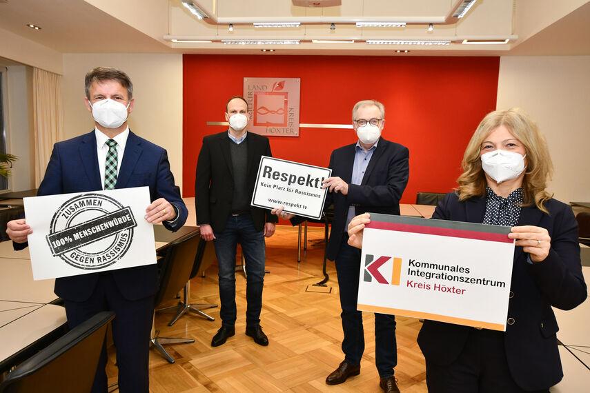 Landrat Michel Stickeln, Domenic Gehle, Klaus Schumacher und Filiz Elüstü halten im Sitzungsraum in der Kreisverwaltung Schilder in der Hand, die auf die Woche gegen Rassismus hinweisen.