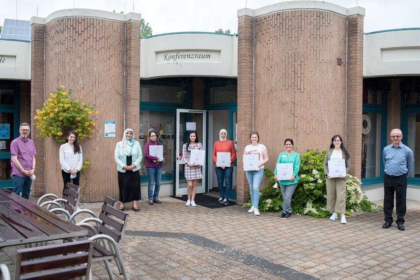 10 Personen stehen vor einem Gebäude mit der Aufschrift 'Konferenzraum'. 6 Personen halten Urkunden in der Hand.