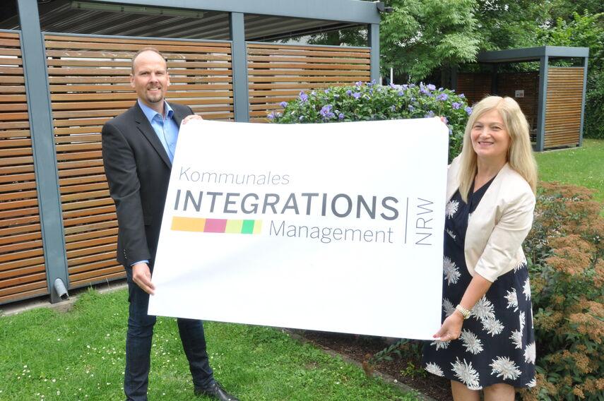 Dominic Gehle und Filiz Elüstü halten einen Banner mit dem Integrationslogo in den Händen.