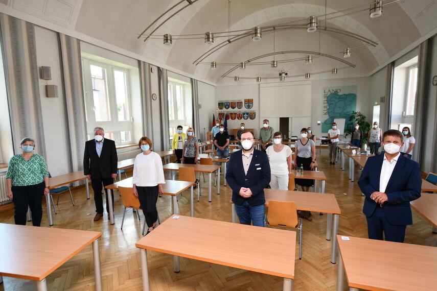 18 Mitglieder des Netzwerks Pflege stehen Coronabedingt mit Maske in der Aula des Kreishauses in Höxter.