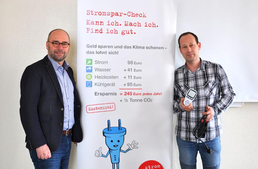 Fachbereichsleiter Michael Werner und Projektleiter Maksim Boschmann vor einem Rollbanner zum Thema Stromspar-Check.