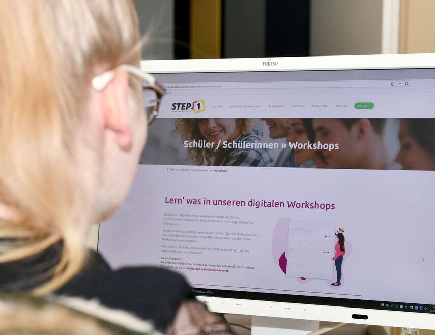 Jana Tölle sitzt vor einem PC und schaut sich die Internetseite mit den Informationen über Step 1 an.