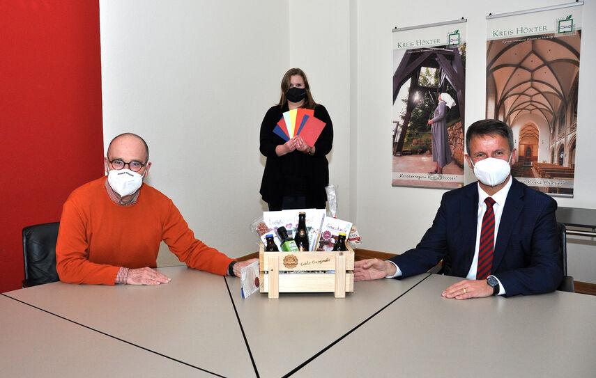 Landrat Michael Stickeln, Michael Werner (Leiter des Fachbereichs Umwelt, Bauen und Geoinformation des Kreises Höxter) und Carolin Röttger (Klimaschutzmanagerin des Kreises Höxter) zeigen die ausgelosten Preise, die an Teilnehmende der Aktion Stadtradeln versendet worden sind.
