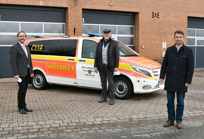 Landrat Michael Stickeln, Dr. Rolf Schulte und Matthias Kämpfer stehen vor einem Notarztwagen.