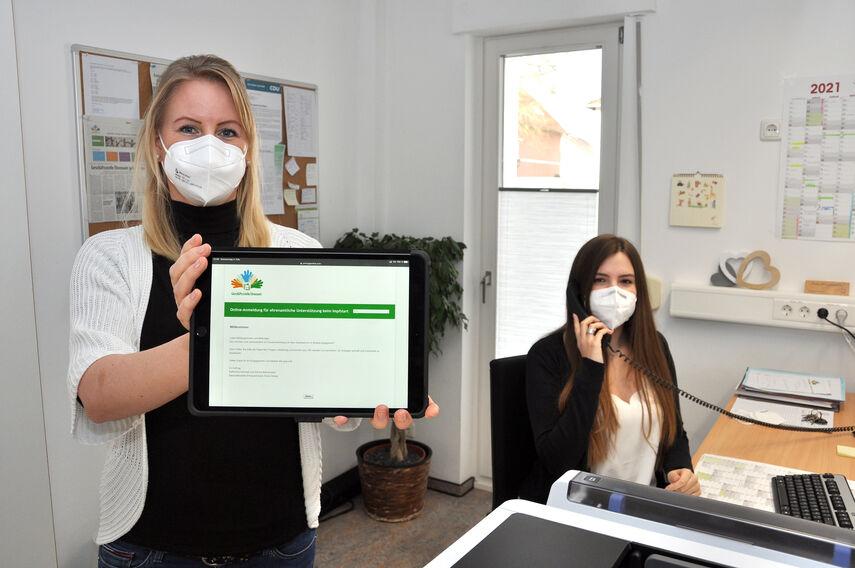 Ehrenamtsmanagerin Katharina Serinelli hält ein Tablet in der Hand, worauf man die neue Internetseite erkennen kann. Dorina Bernsmann sitzt am Schreibtisch und führ ein Telefonat.