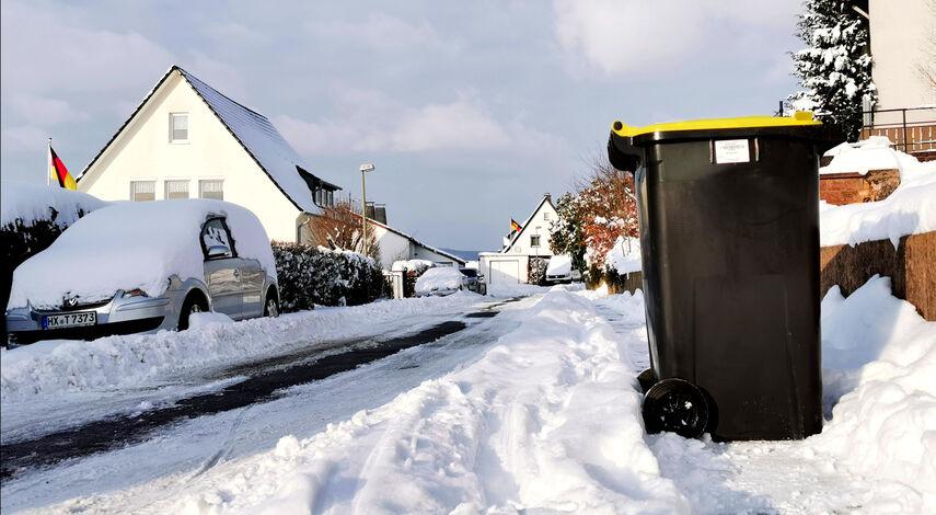 Mülltonne in schneebedeckter Straße.