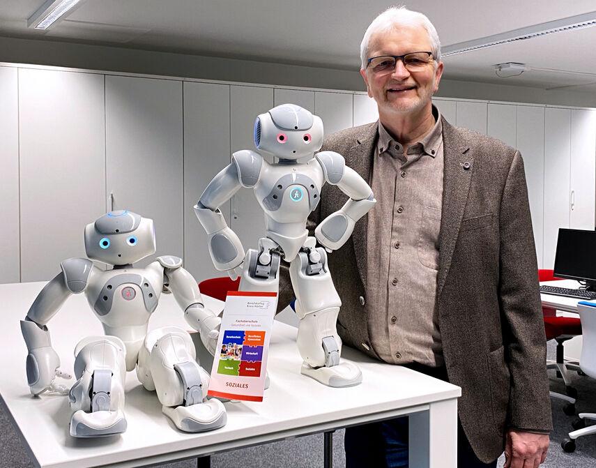 Bildungsgangleiter Dieter Rauchmann zeigt 2 Roboter die auf einem Tisch stehen.