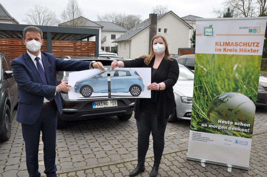 Landrat Michael Stickeln und Klimaschutzmanagerin Carolin Röttger halten gemeinsam ein Foto eines Autos in den Händen. Das Foto ist in der Mitte geteilt, was symbolisch für das 'Car-Sharing' stehen soll.