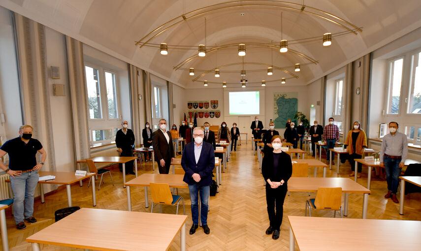 21 Personen des Kulturbeirats des Kreises Höxter stehen in der Aula des Kreishauses.