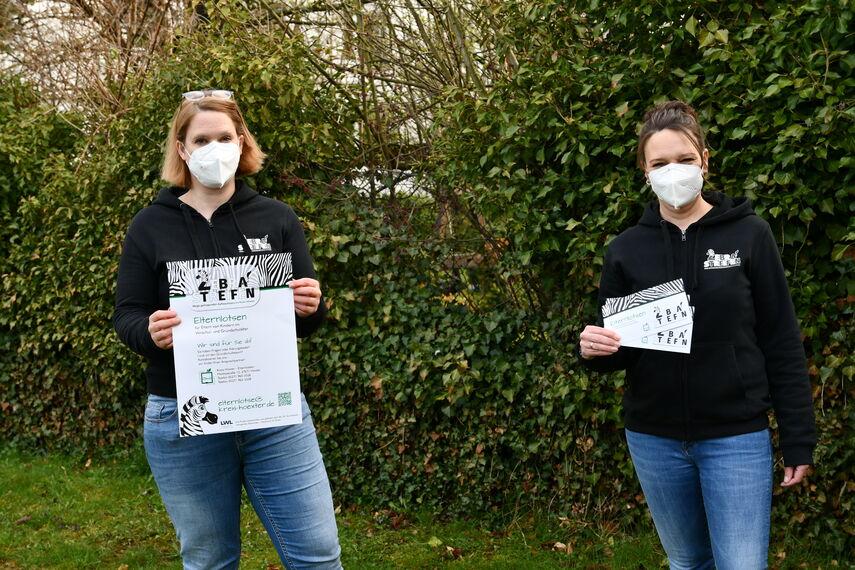 Sandra Wegener und Silke Merkel halten das Plakat und den Flyer 'Zebrastreifen' in den Händen.
