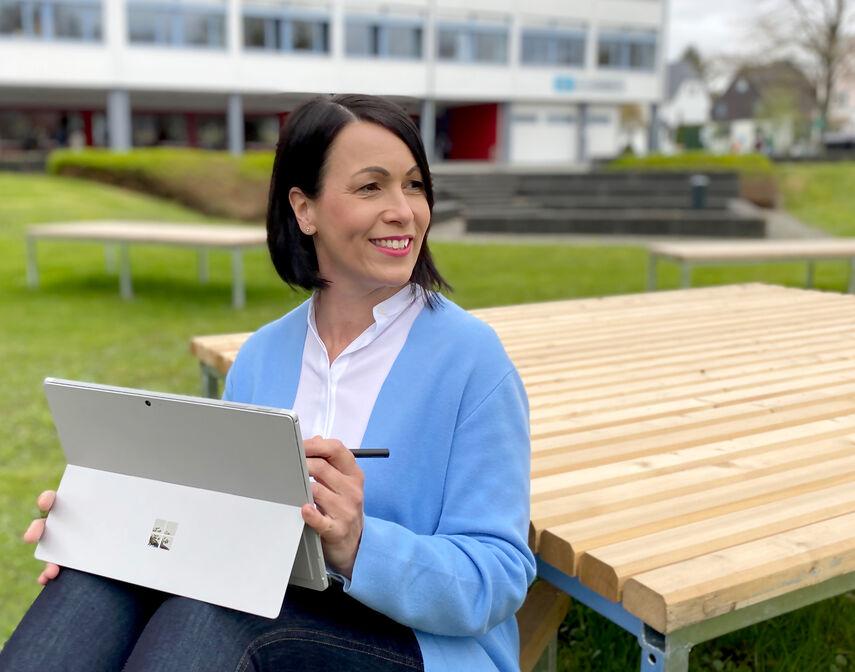 Kerstin Eller sitzt mit einem Tablet in der Hand auf einer Bank vor einer Schule.