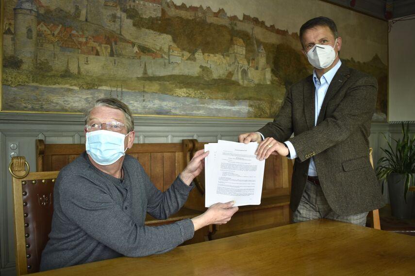 Landrat Michael Stickeln und Dr. Andreas Knoblauch-Flach halten zusammen den Förderbescheid über 600.000 Euro in die Kamera.