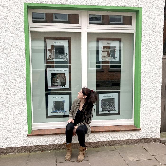 Eine junge Dame sitzt vor einem Fenster und schaut sich die Werke eines Künstlers an, die im Schaufenster dekoriert sind.