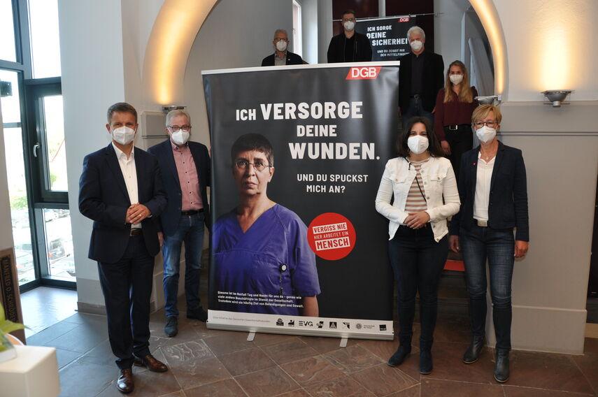 12 Personen stehen um einen Rollbanner herum, der auf die Aktion 'Vergiss nie, hier arbeitet ein Mensch' aufmerksam macht.