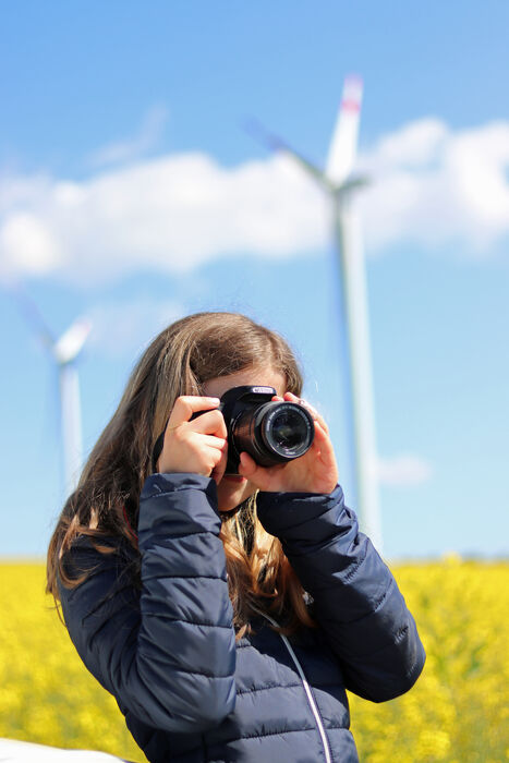 Eine junge Dame fotografiert eine Windkraftanlage. Sie steht in einem Rapsfeld.