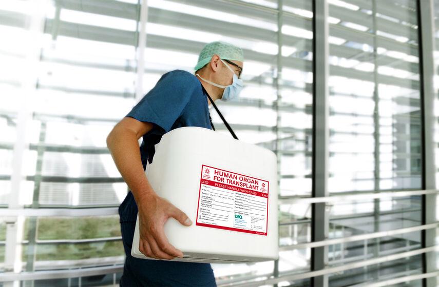 Ein junger Mann trägt eine Kist mit der Aufschrift Organspende